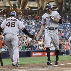 San Francisco Giants' Hunter Pence gets a low-five from Pablo Sandoval as he crosses home plate with a three-run home run during the first inning of a baseball game against the San Diego Padres on Saturday, Sept. 29, 2012, in San Diego.