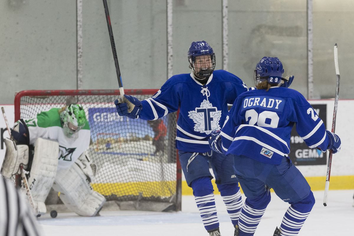 Emily Fulton, wearing Furies home blue uniform and holding her stick up in the air, smiles at fellow Fury Jessica O'Grady, whose back is to the camera. Markham Thunder goalie Liz Knox hangs her head in the background.