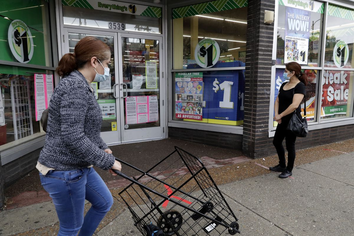 A woman waits in line to shop at a Dollar Tree store in Chicago.