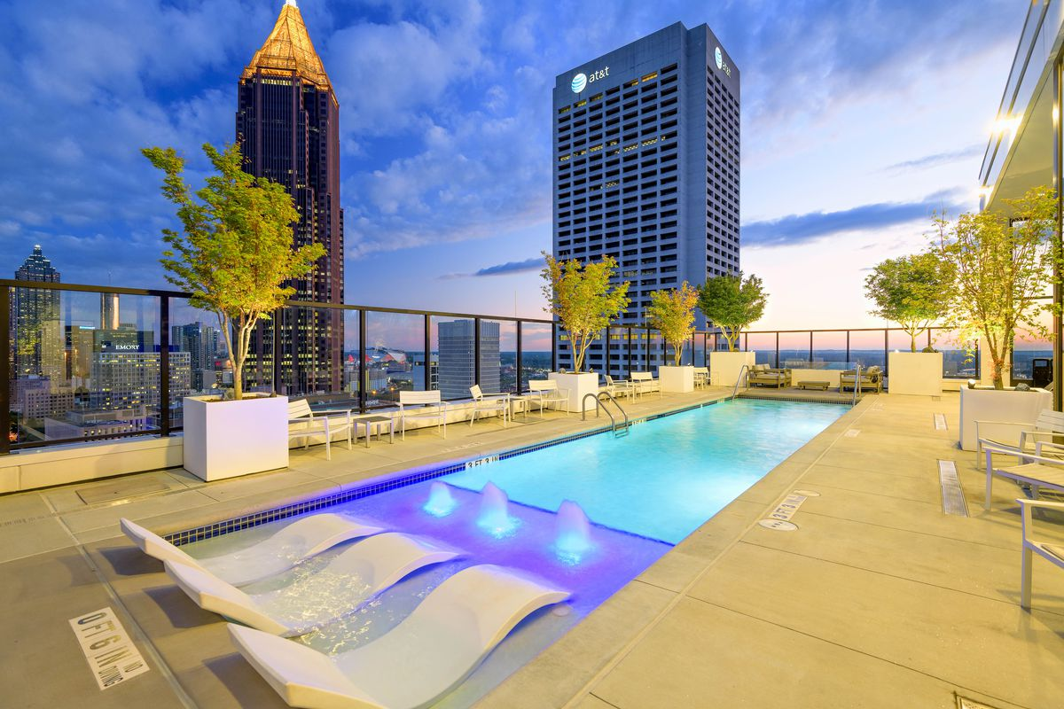 A pool atop a tower in Atlanta with concrete and lighted water.