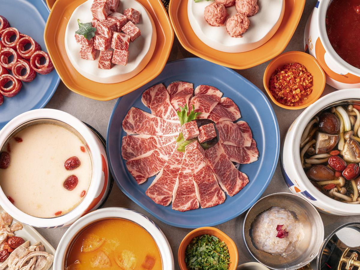 A hot pot spread at the Dolar Shop full of meats and broths