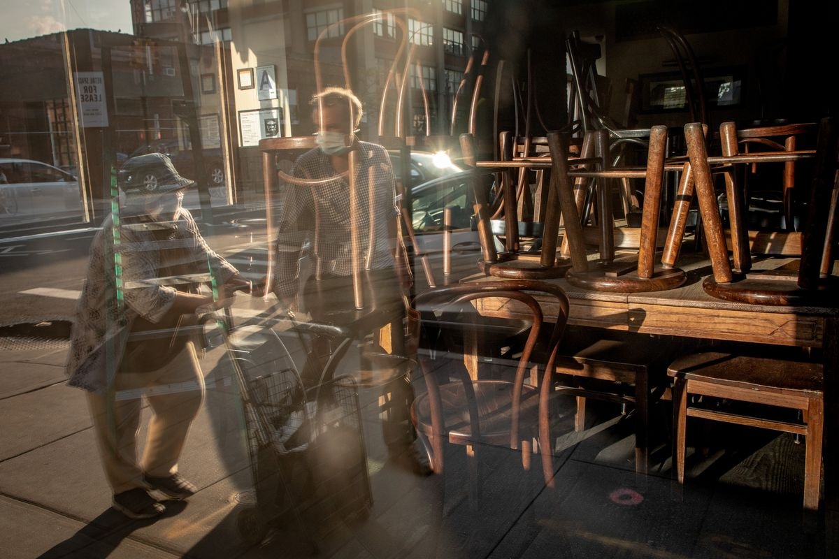 A window looking into a closed restaurants, where stools are on top of a table and a man with a mask is in the reflection.