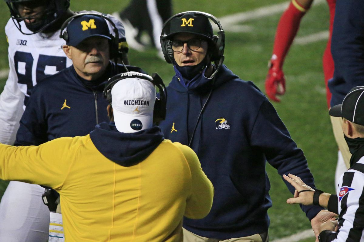 Head coach Jim Harbaugh of the Michigan Wolverines talks with coaches during the fourth quarter at SHI Stadium on November 21, 2020 in Piscataway, New Jersey.