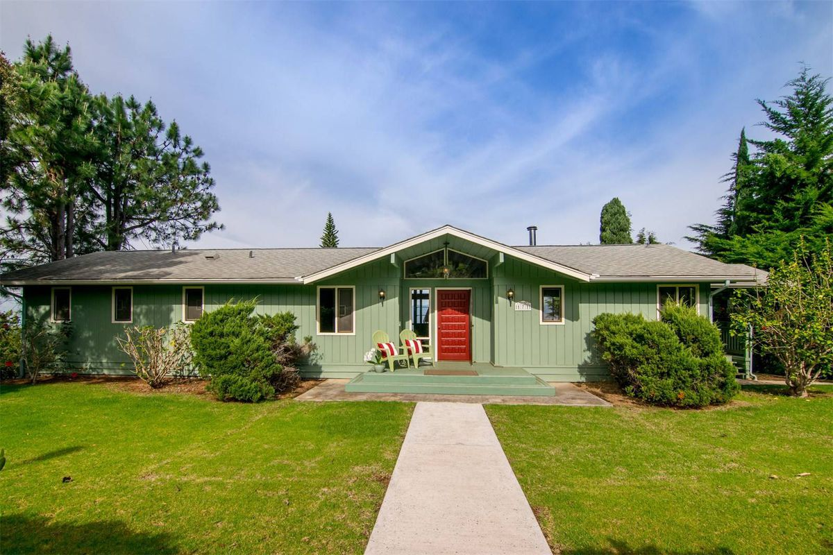 Single-level ranch-style home with pitched entryway on grassy lot.