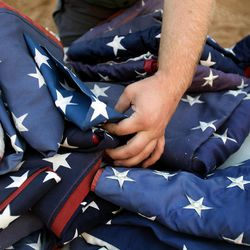 Hundreds of American flags are delicately handled prior to a retirement ceremony at the Davis County Fair in Farmington on Thursday, Aug. 15, 2013. Participants in the ceremony included the American Legion, Utah National Guard, Boy Scouts and Girl Scouts, and members of Davis County fire departments.