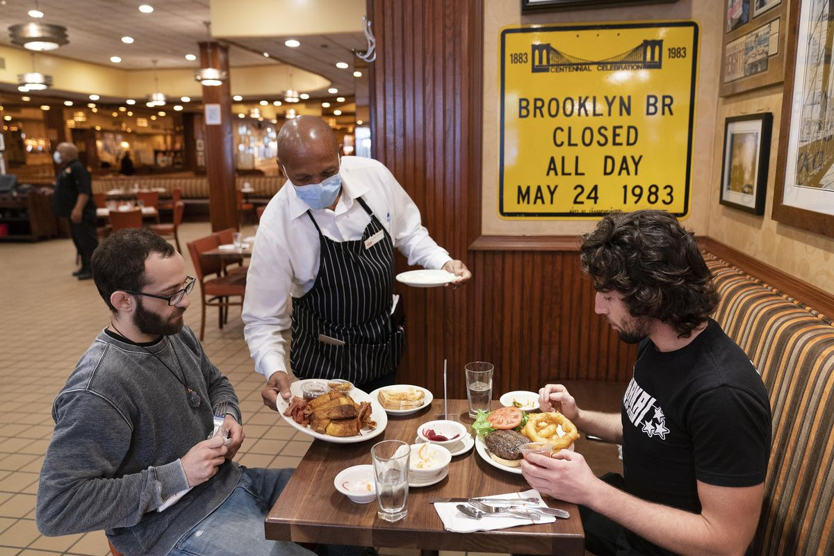 In this Sept. 30, 2020, file photo, Waiter Lenworth Thompson serves lunch to David Zennario, left, and Alex Ecklin at Junior's Restaurant in New York. New York City will soon require proof of COVID-19 vaccinations for anyone who wants to dine indoors at a restaurant, see a performance or go to the gym, Mayor Bill de Blasio announced Tuesday, Aug. 3, making it the first big city in the U.S. to impose such restrictions.