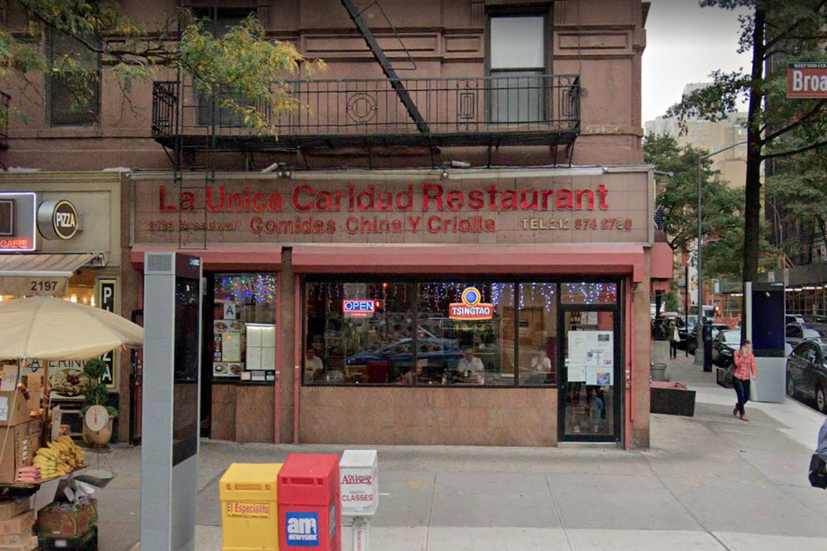 The red storefront with the restaurant's name is red lettering on the building