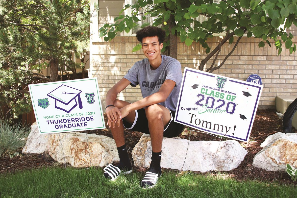 """A young man sits on a landscaping rock outside a house with signs on either side of him celebrating his graduation. """"Home of a Class of 2020 ThunderRidge Graduate,"""" one sign reads."""