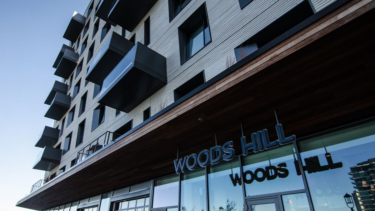 """The exterior of a luxury condo building. Signage reading """"Woods Hill"""" is visible in front of the glassy first level."""