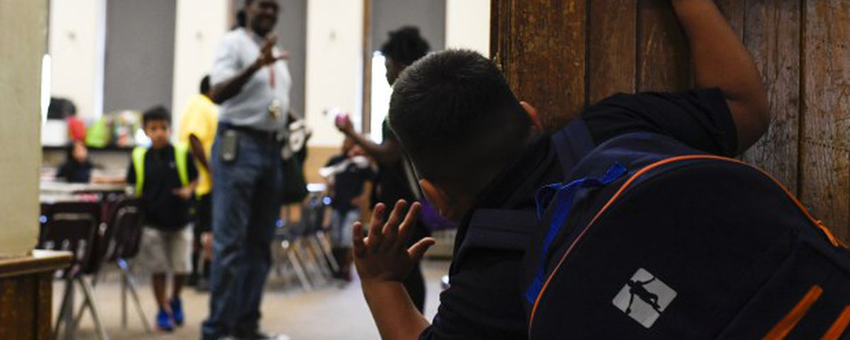 Sebastian Cruz waves to Rev. Leon Kelly as he works with children in a classroom during his after-school program at Wyatt Academy in September 2018.