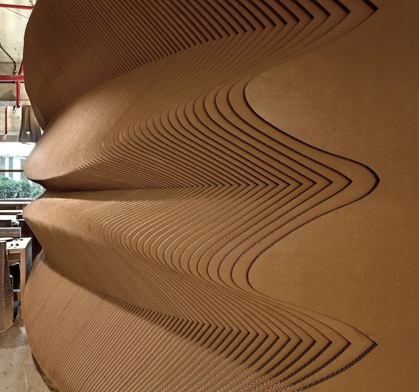 A wall made out of layers of corrugated cardboard. The cardboard is arranged in a layered pattern creating a ridged, curved shape on the wall.