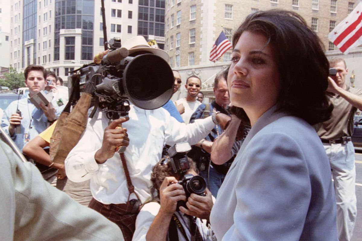 Photograph of Monica Lewinsky, surrounded by reporters, in 1998.