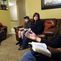 Clayton Hunt, right, explains a passage from The Book of Mormon as his wife Kit, second from right, along with daughter Aspen (15) and son Christian (13) follow along in their home in Bountiful on Thursday, Dec. 26, 2013.