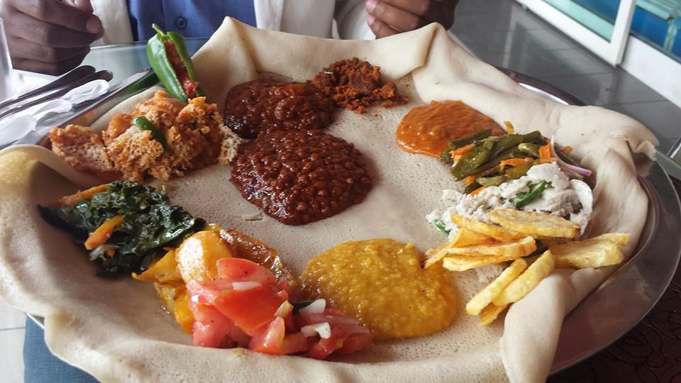 A wide, round injera is piled with curried lentils, braised goodies, rich sauces, bright greens, creamy sauce and more