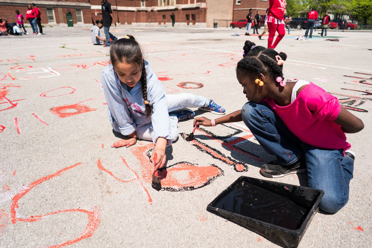 Montessori School of Englewood students paint the name of one of the 291 schools across the United States that has been affected by gun violence since the Sandy Hook shooting in 2012 as part of the Schools Say Enough art installation on May 16, 2018. | Ma