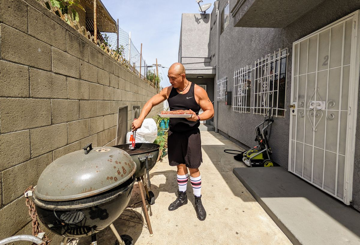Johneric Concordia scrapes a kettle grill with a piece of crumpled aluminum foil to clean it before placing seasoned beef.