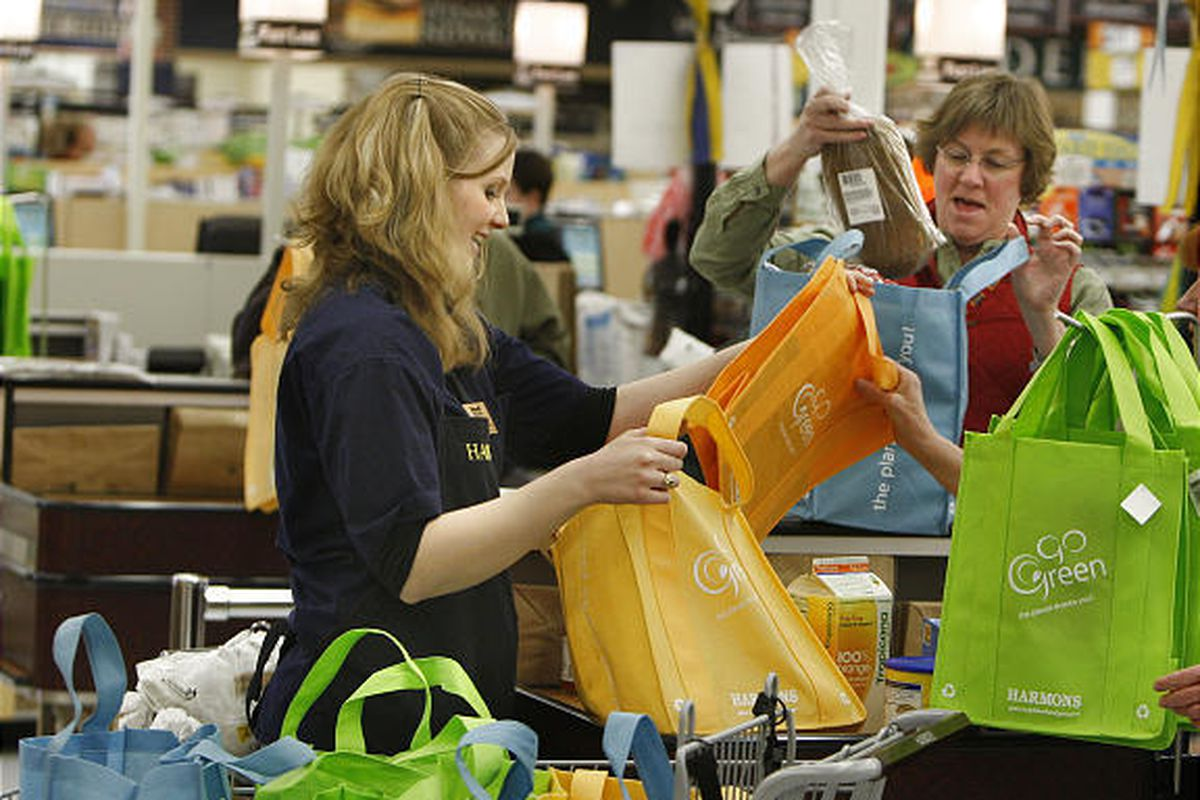 """Janice Rampton has her """"Go Green"""" grocery bags filled by Laura Shackelford at Harmons grocery store."""