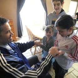 Jeff Griffin has a surprise for his daughters Karlee, 8, left, and Savanna, 10, as brother Bradley, 12, looks over their shoulder in their home in West Jordan on Thursday, Feb. 27, 2014.