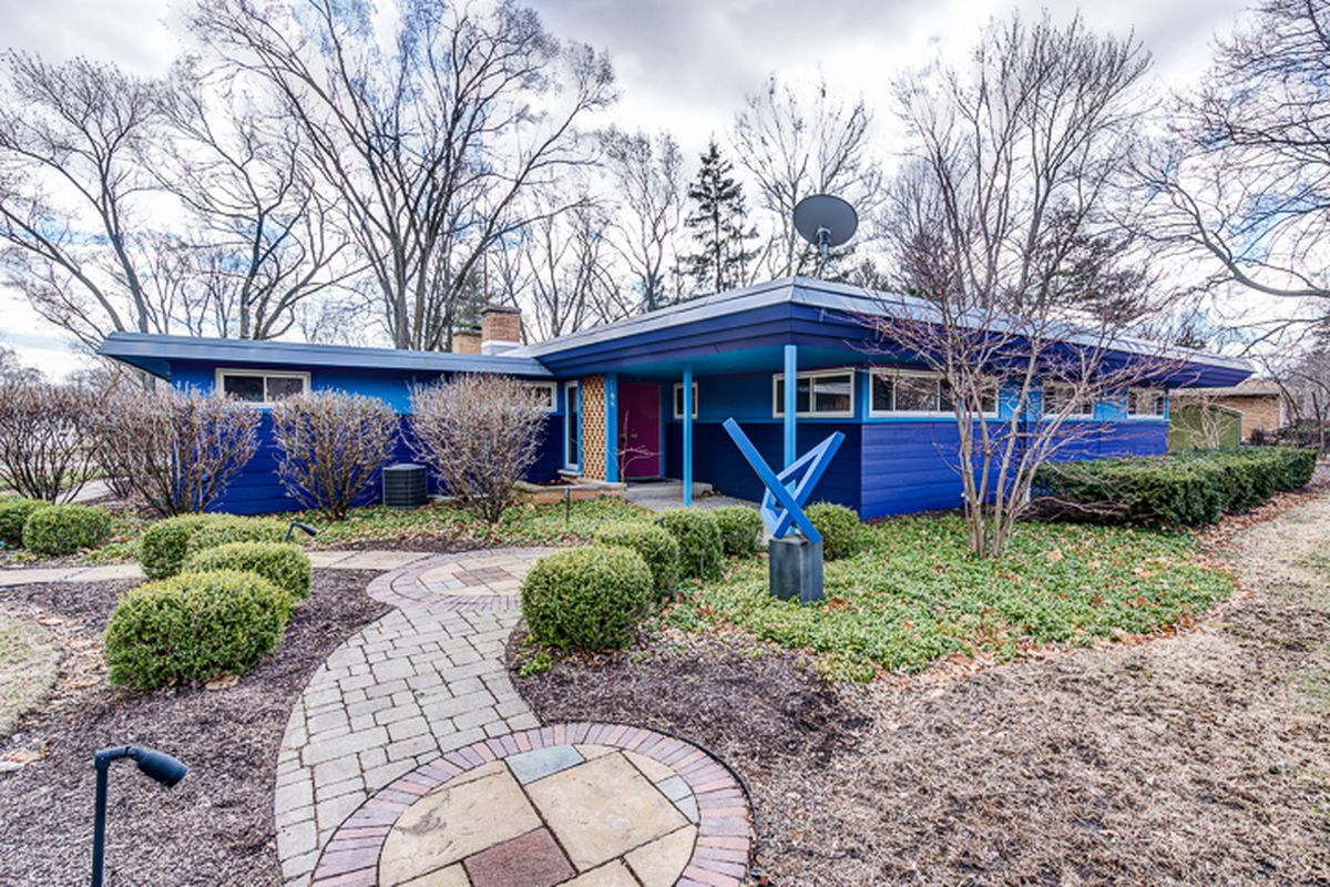 Single story bungalow home with overhanging flat roof painted bright blue.