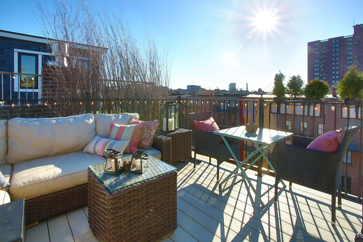 The corner area of a roof deck with a couch and a table with two chairs.