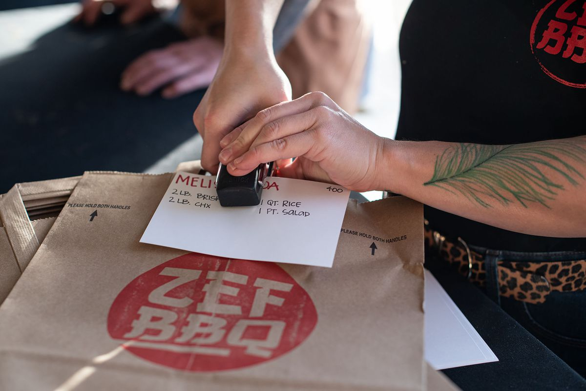 Two hands staple orders to brown paper bags to get ready for a meal.
