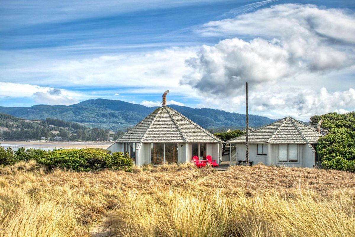 Wide shot of two polygonal structures painted light grey with pointed roofs. Beach grass lies in the foreground, with mountain and bay views behind it.