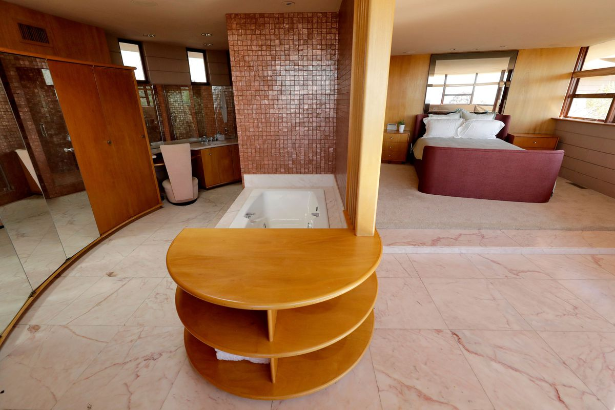 A master suite has a bed on one side and a pink bathroom on the other.