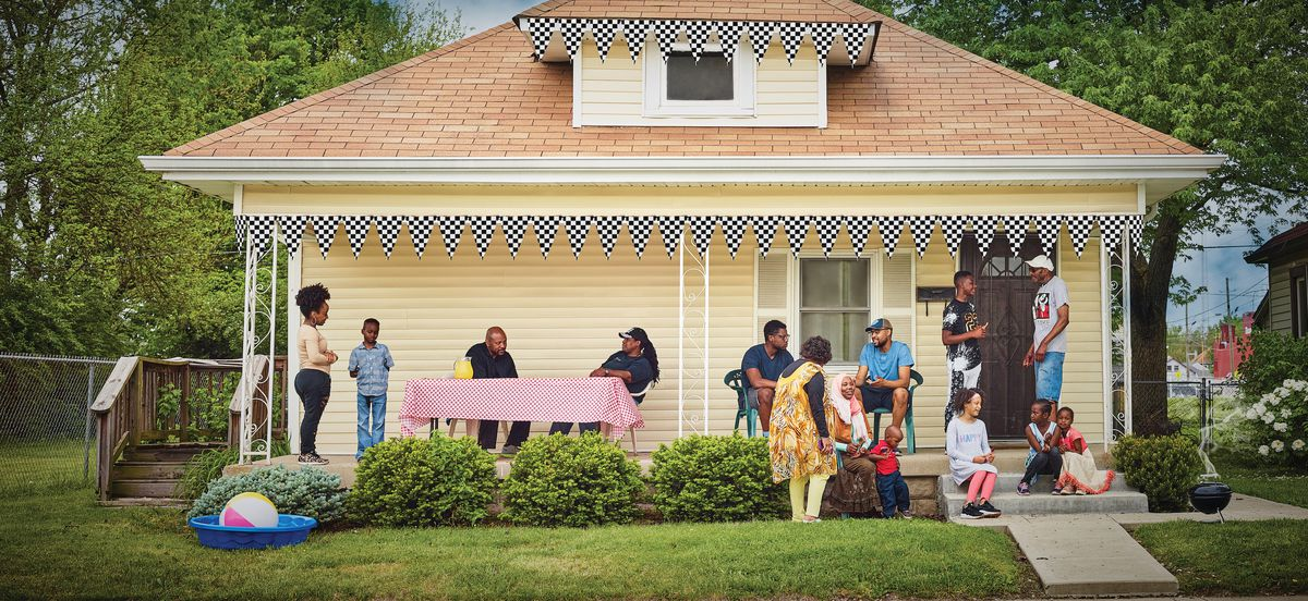 A gathering of neighbors at a house party in the front of a home with yellow aluminum siding.