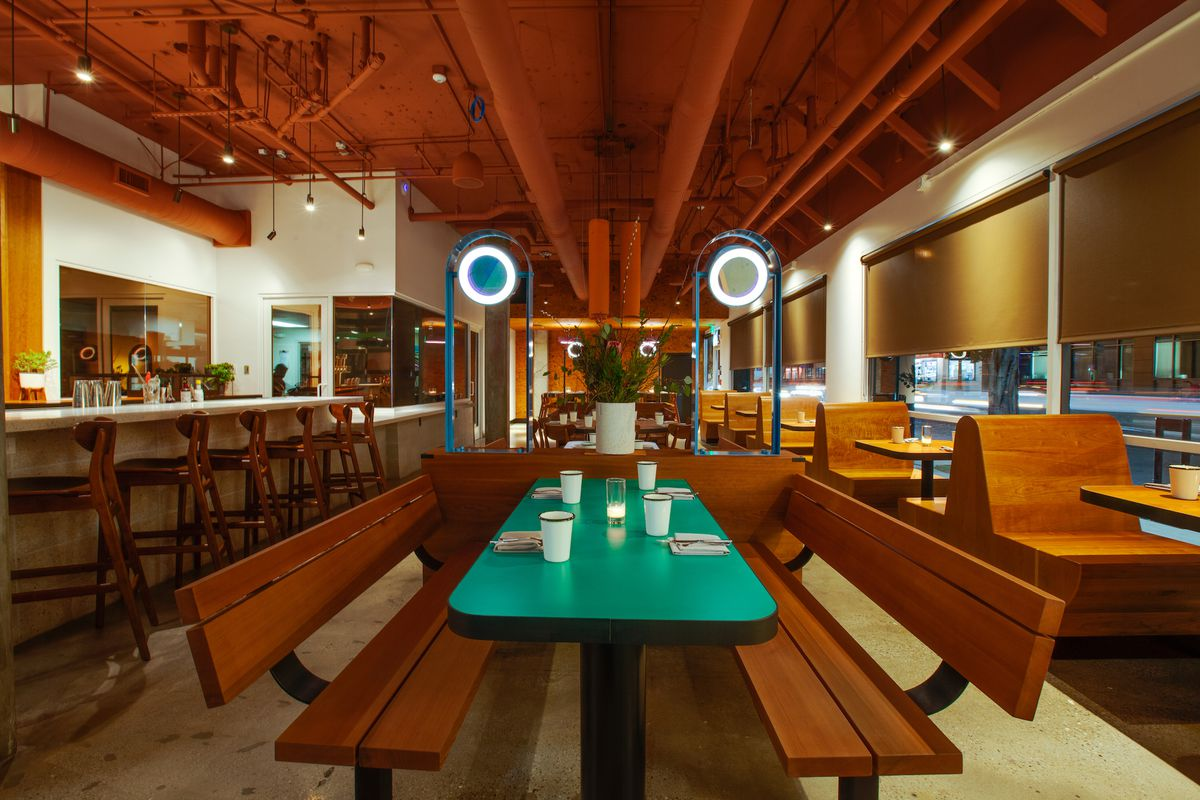 A teal wooden booth with tall ceilings at a new restaurant.
