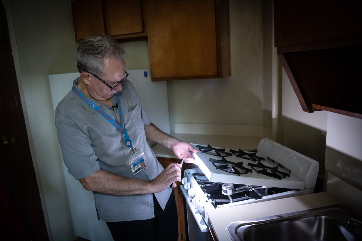 NYCHA Chair Gregory Russ looks at a stove in a complex, August 13, 2019.