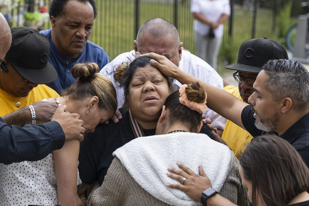 Gyovanni's mother, Minerva Arzuaga, is comforted during a prayer at a press conference address the gun violence in communities at the memorial site for Yasmin Perez and Gyovanni Arzuaga near 3300 W. Division St in Humboldt Park.