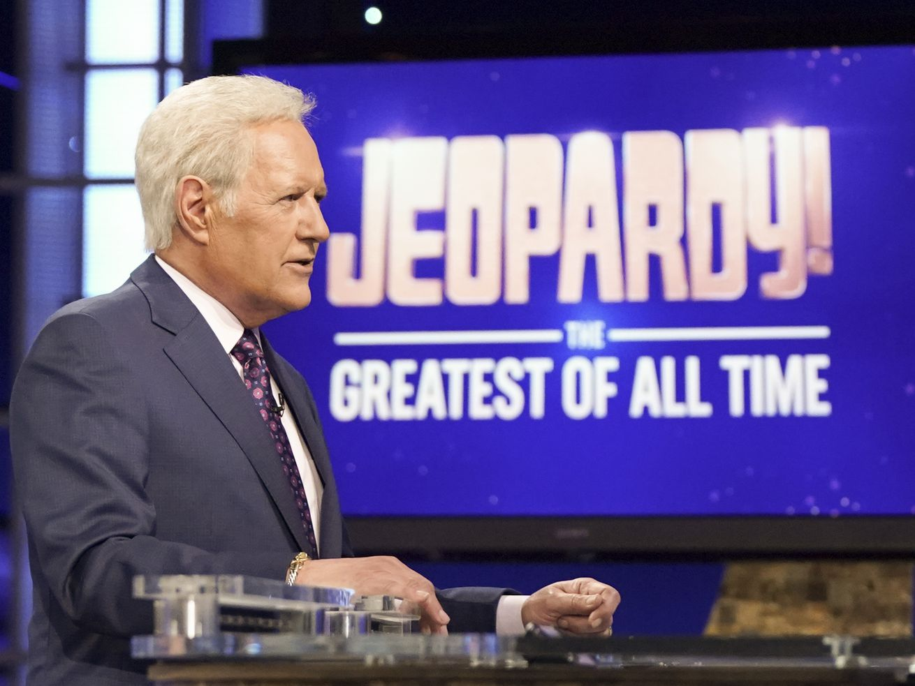 "In a dark grey suit, white button-down, and red tie, a white-haired Alex Trebek stands in front of a screen reading ""Jeopardy! The Greatest of All Time."""