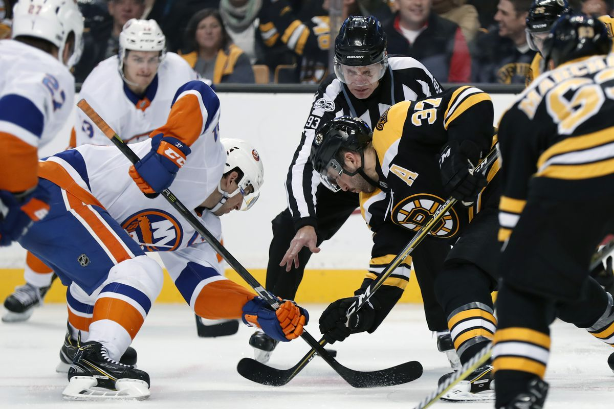New York Islanders center John Tavares (91) and Boston Bruins center Patrice Bergeron (37) take the face off from linesman Brian Murphy (93) during a game between the Boston Bruins and the New York Islanders on December 9, 2017, at TD Garden in Boston, Massachusetts.