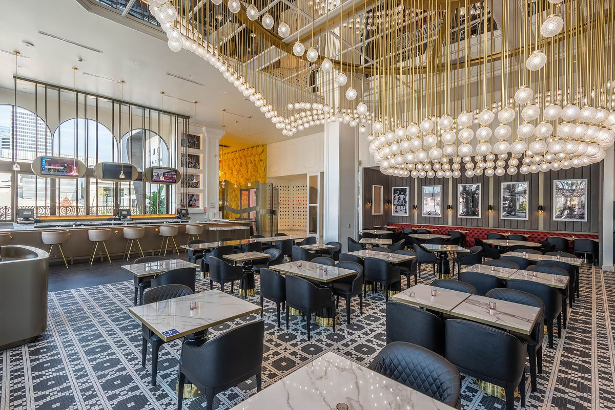 A bright gold chandelier and tiled floor inside a massive new restaurant.