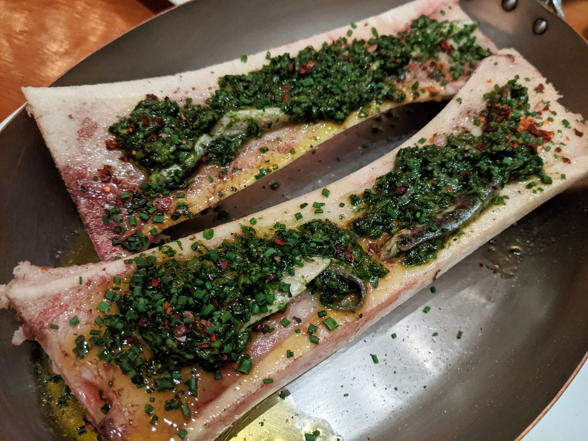 Two long bones filled with marrow are topped with an oily collection of minced herbs.