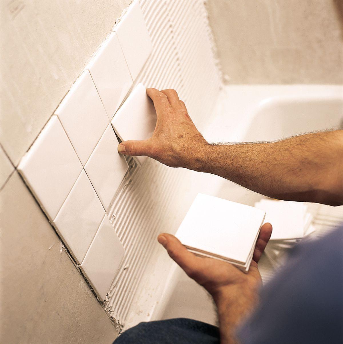 Man Installs Ceramic Tiles Onto Tile Mastic