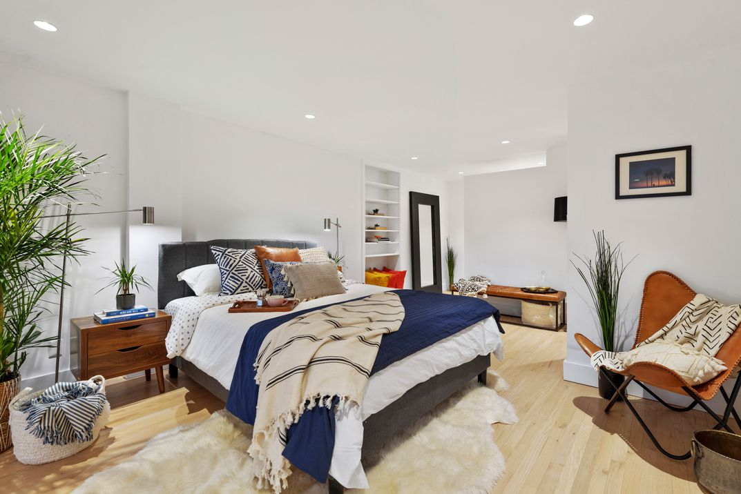 A bedroom with hardwood floors, white walls, a large bed, a chair, and a planter.