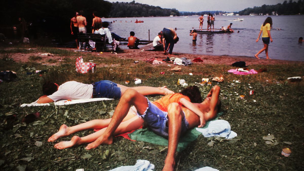 Young people relaxing by a lake during the the Woodstock music festival, 1969.