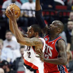 Portland Trail Blazers' LaMarcus Aldridge (12) pulls down a rebound in front of New Jersey Nets' Johan Petro (27) in the first quarter of an NBA basketball game, Wednesday, April 4, 2012, in Portland, Ore.