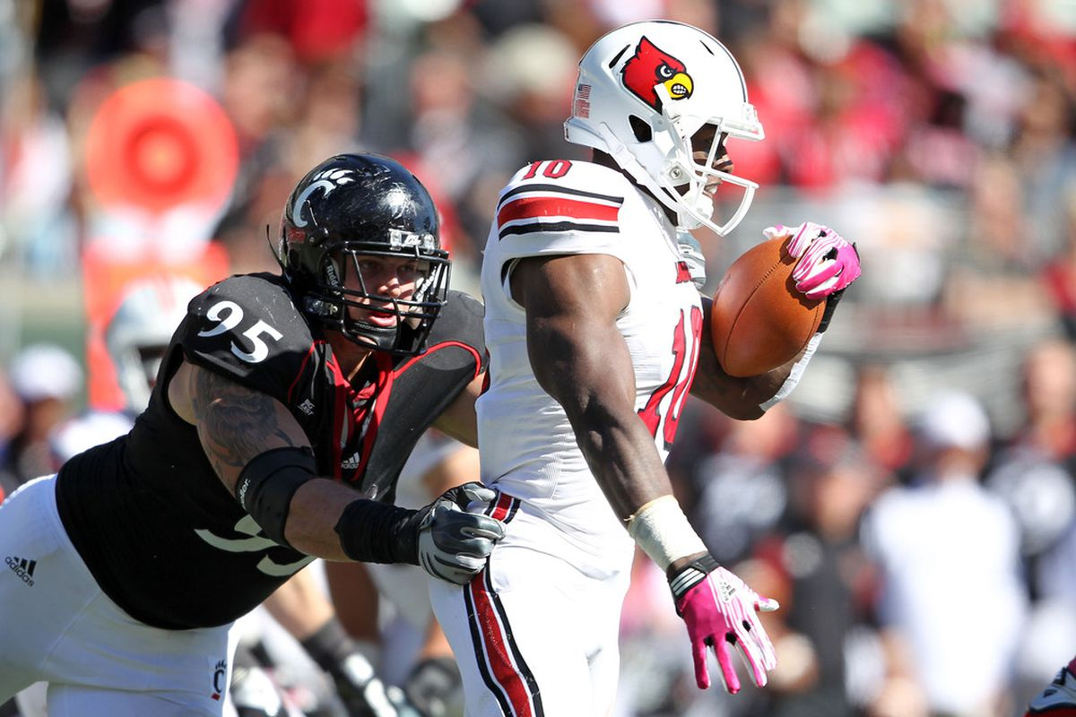 CINCINNATI, OH - OCTOBER 15: Derek Wolfe #95 of the Cincinnati Bearcats tackles Dominique Brown #10 of the Louisville Cardinals during the game at Paul Brown Stadium on October 15, 2011 in Cincinnati, Ohio.  (Photo by Andy Lyons/Getty Images)