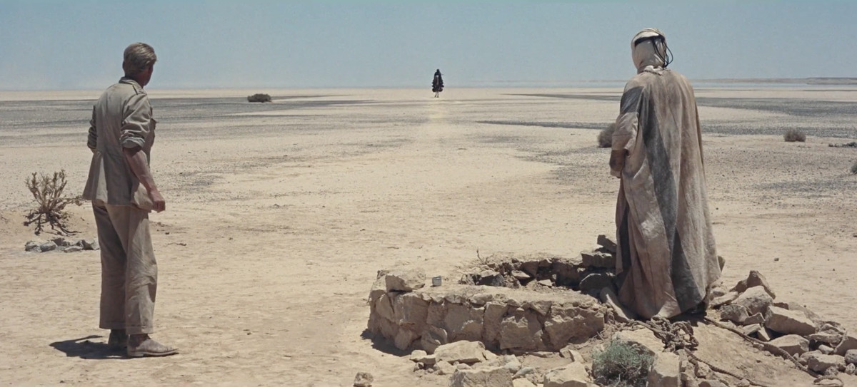 Two men in drab, dirty clothing stand with their backs to the camera in a barren desert that's the same color as their clothes, as a lone figure approaches in the far distance.