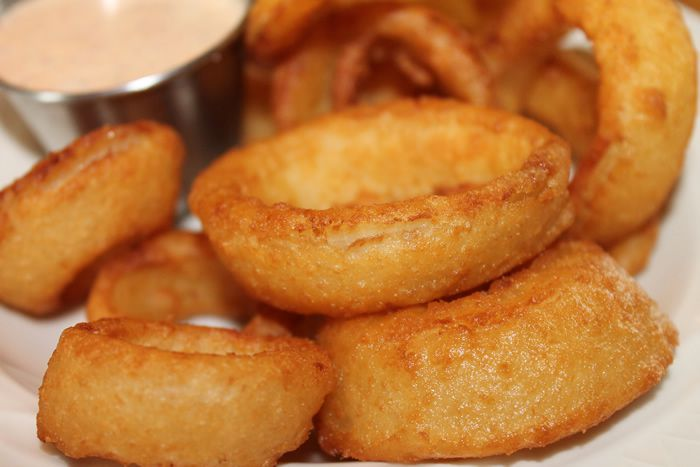 Large fried onion rings with dipping sauce in the background