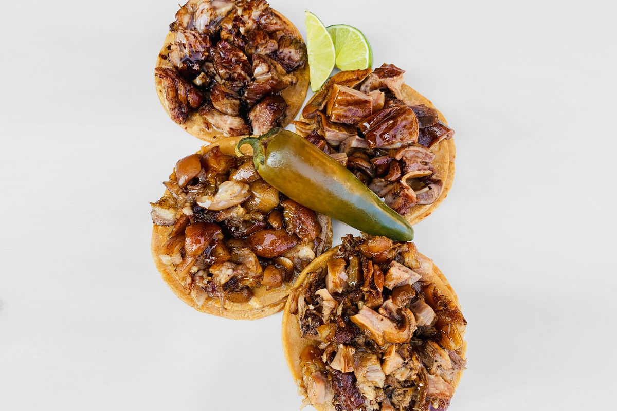Four meat-laden tacos laid out on a white background with a large jalapeno pepper placed in the center