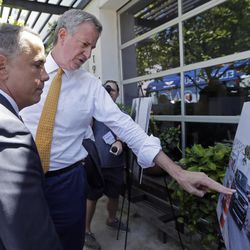 New York City Mayor Bill de Blasio, right, points to a photo as Miami Beach Mayor Philip Levine, left, looks on during a tour showing where the city has raised streets and installed pumps to combat rising tides, Friday, June 23, 2017, in Miami Beach, Fla. The U.S. Conference of Mayors opens its annual meeting Friday in Miami Beach. Mayors of cities with populations of 30,000 or more will discuss plans to reduce the nation's carbon footprint and protect immigrant families.
