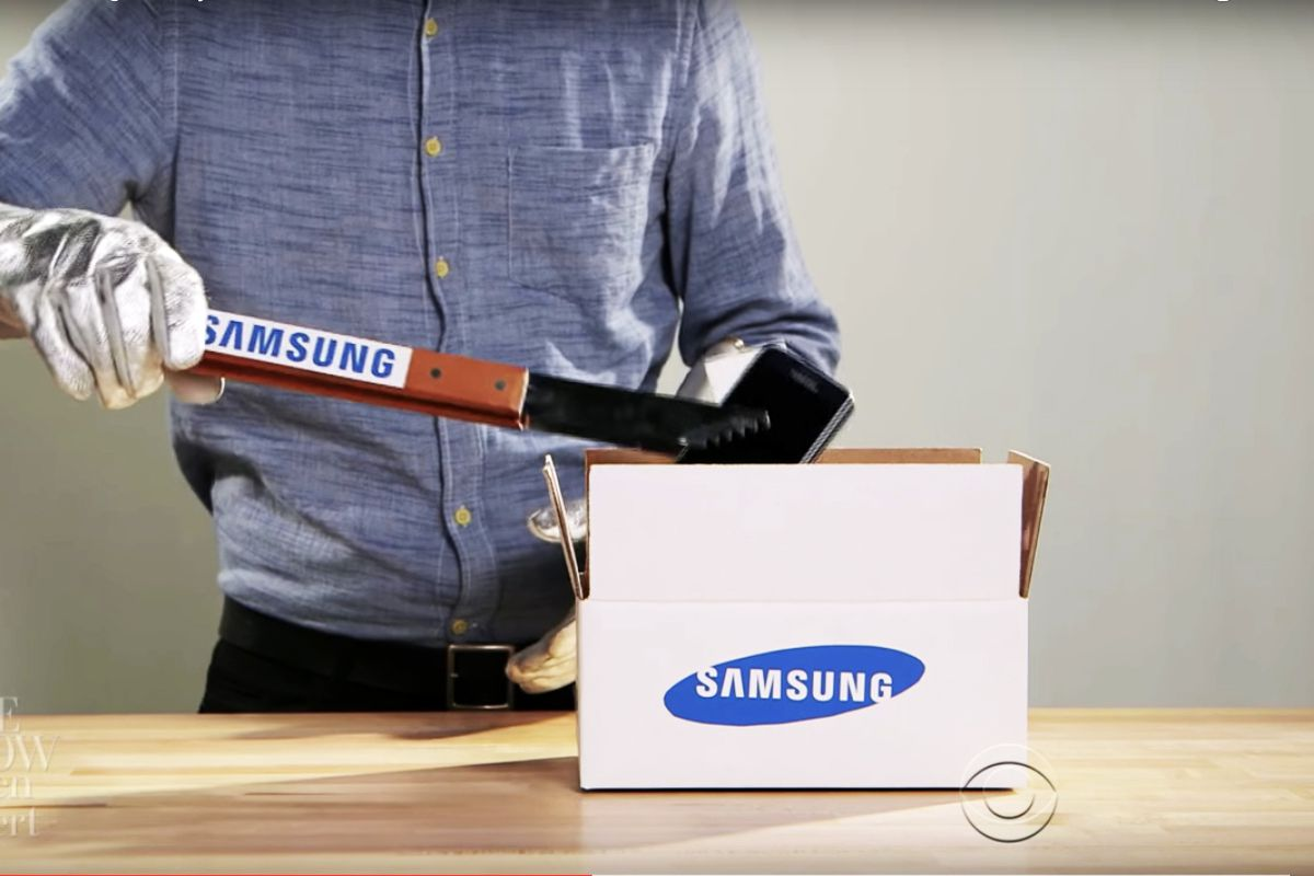 A clip from Colbert's video in which you see a man wearing aluminum gloves, holding tongs emblazoned with the Samsung logo, gently putting a phone into a Samsung box.