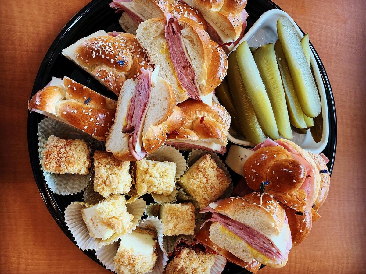 A platter of sandwiches, pickles, and other bites.
