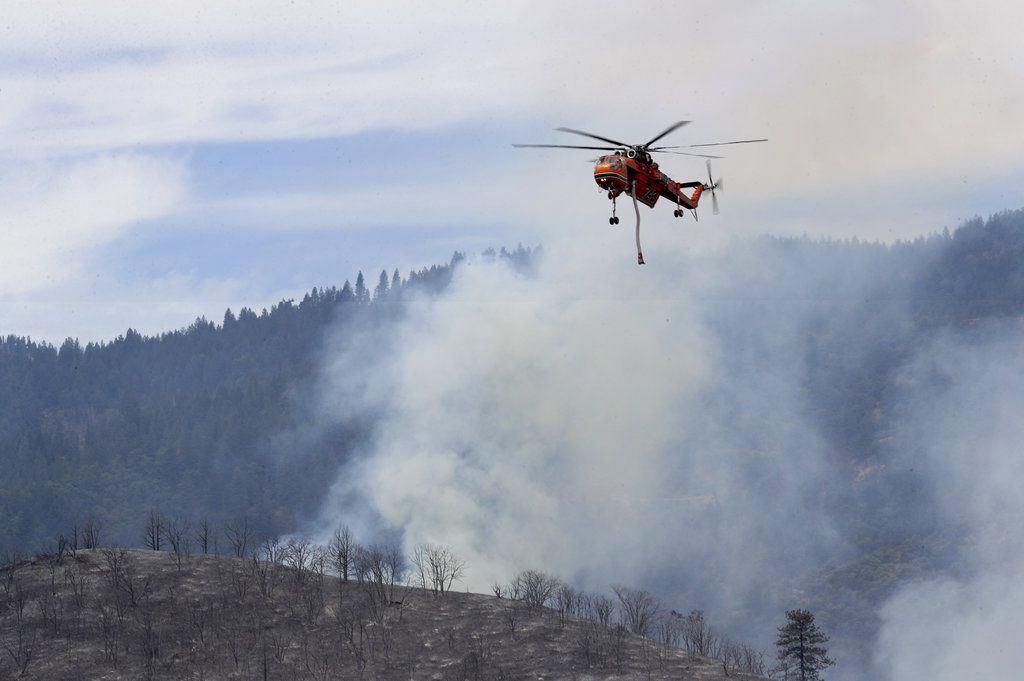 A helicopter flies above the Klamathon Fire near the Oregon-California border and Hornbrook, Calif., Friday, July 6, 2018.   Greg Barnette/The Record Searchlight/USA TODAY Network via AP