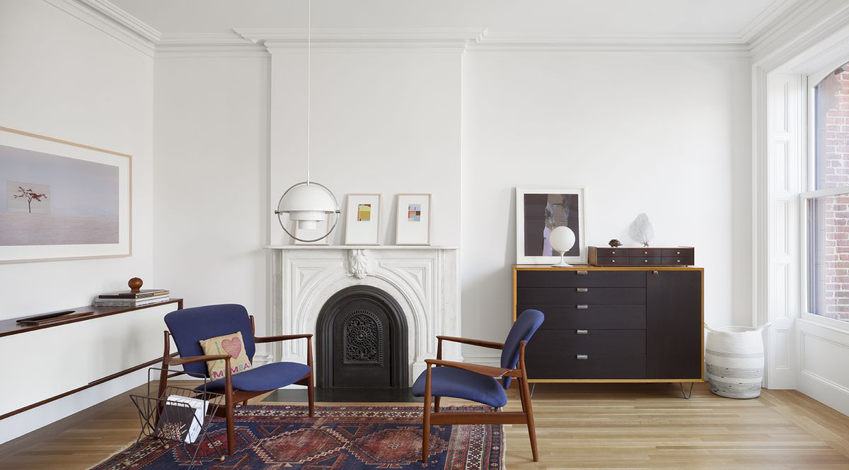 A dresser from George Nelson's Basic Cabinet Series for Herman Miller and a vintage Louis Weisdorf Multi Lite pendant lamp frame a sitting area in the second-floor master bedroom. The artwork on the mantel was done specifically for the house by Kristin Texeira.