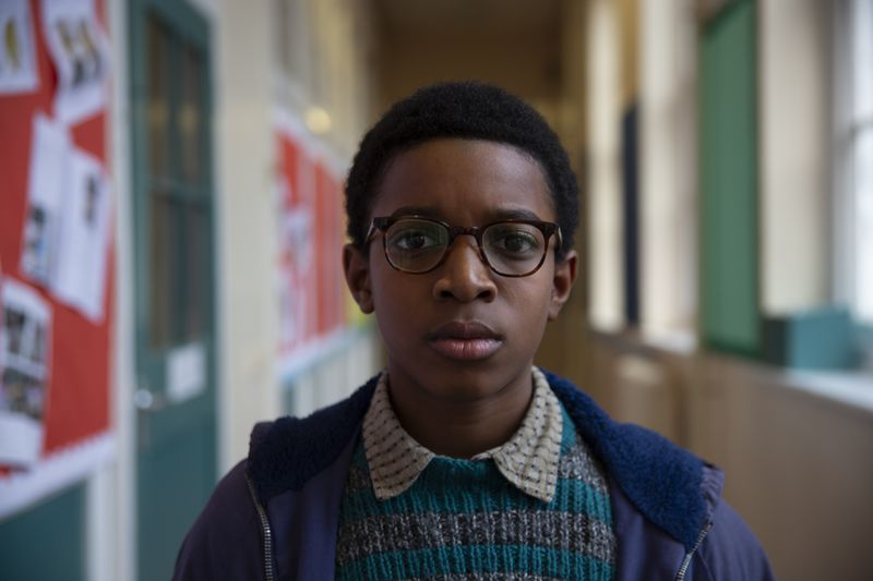 A young boy wearing glasses looks straight ahead.