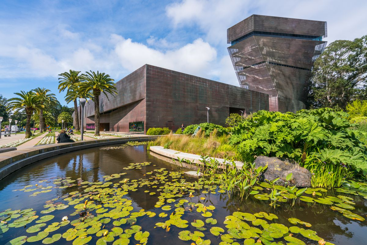 The exterior of the De Young Museum in San Francisco. The building has a funnel shaped tower. In front of the building are palm trees and a pond with water lilies.
